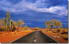 Dark storm clouds gather over Australia's Lasseter Highway as it winds through the red sand desert