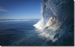 Female surfer in the tube of a breaking wave, Fiji