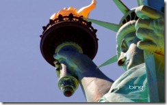 Detail of the Statue of Liberty showing the torch, flame, face, crown, robe and hand holding the tablet