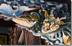 Ornately carved wooden bracket depicting Vietnamese dragon, above doorway, Hoi An, Vietnam